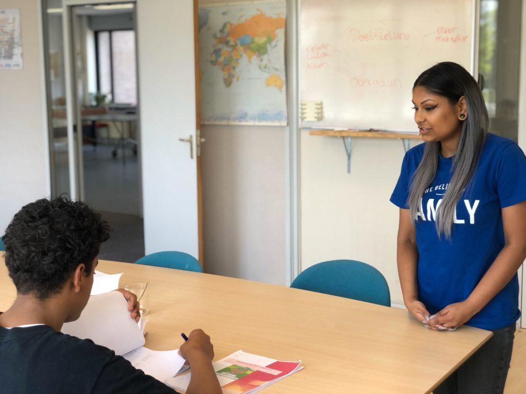 Stagiair geeft uitleg aan jongeren tijdens de huiswerkbegeleiding op het kantoor van YETS